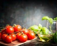 Manojo fresco de los tomates de cereza con albahaca y aceite en el fondo rústico oscuro, vista lateral Imágenes de archivo libres de regalías