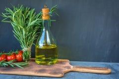 Manojo fresco del jardín de romero, una botella de aceite del aceite o de romero de oliva y de tomates de cereza en una vieja tab Fotos de archivo libres de regalías