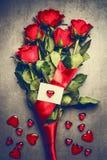 Manojo grande de rosas rojas con la tarjeta de felicitación en blanco blanca con los corazones, visión superior Símbolos del amor Fotos de archivo libres de regalías