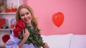 Manojo hermoso feliz de la tenencia de la mujer de rosas rojas y de sonrisa a la cámara, romance almacen de video