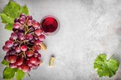 Manojo maduro de la uva con las hojas y el vidrio de vino en el backgro de piedra fotos de archivo