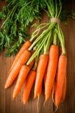 Manojo orgánico fresco de las zanahorias en fondo de madera imagenes de archivo