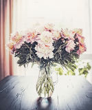 Manojo precioso de las peonías en florero en la tabla en el fondo de la ventana, aún vida Foto de archivo libre de regalías