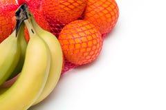 Manojos de naranjas y de plátanos Imagen de archivo