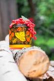 Manojos de pasa roja madura en pote de madera decorativo, pintados en el estilo de Khokhloma Fotografía de archivo