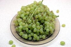 Manojos de uva verde madura en placa transparente en el primer de la tabla de cocina Imagenes de archivo