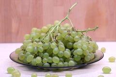 Manojos de uva verde madura en placa transparente en el primer de la vista delantera de la tabla de cocina Imágenes de archivo libres de regalías