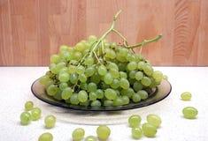 Manojos de uva verde madura en placa transparente en el primer de la vista delantera de la tabla de cocina Fotos de archivo libres de regalías