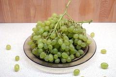 Manojos de uva verde madura en placa transparente en el primer de la vista delantera de la tabla de cocina Imagen de archivo