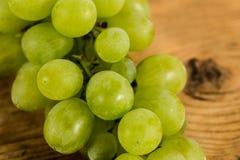 Manojos de uvas en una tabla de madera rústica Imagenes de archivo