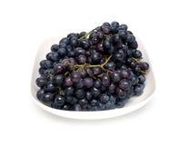 Manojos maduros de la uva en el cuenco blanco aislado Fotografía de archivo
