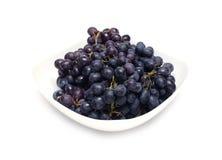 Manojos maduros de la uva en el cuenco blanco aislado Fotos de archivo libres de regalías