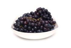 Manojos maduros de la uva en el cuenco blanco aislado Imágenes de archivo libres de regalías
