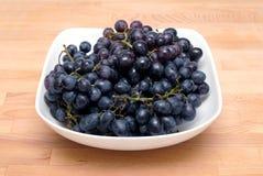 Manojos maduros de la uva en el primer blanco del cuenco Foto de archivo libre de regalías