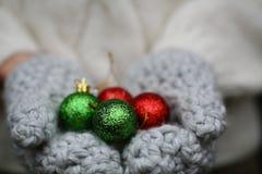 Manoplas con las decoraciones de la Navidad Fotografía de archivo libre de regalías