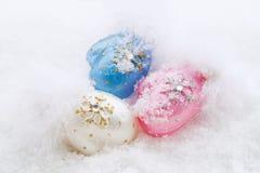 Manoplas de cristal de la decoración de la Navidad en un fondo de la nieve natural Imagen de archivo