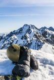 Manoplas, hacha de hielo, casco y vidrios en las montañas Imágenes de archivo libres de regalías