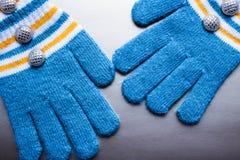 Manoplas hechas punto azules en un fondo p?rpura foto de archivo libre de regalías