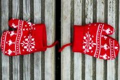 Manoplas hechas punto rojo de la Navidad con motivos del copo de nieve Fotos de archivo