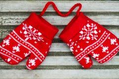 Manoplas hechas punto rojo de la Navidad con motivos del copo de nieve Imágenes de archivo libres de regalías