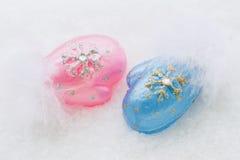 Manoplas miniatura azules y rosadas en una nieve natural del fondo blanco La Navidad, Año Nuevo Foto de archivo
