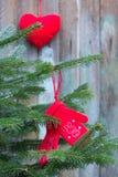 Manoplas rojas hechas punto en el árbol de navidad Fotos de archivo