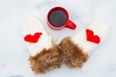 Manoplas y taza roja en la nieve Fotografía de archivo