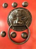 Manopola cinese del leone del bronz sulle porte rosse del portone Immagine Stock