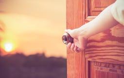 Manopola della porta aperta della mano delle donne o aprire la porta fotografia stock libera da diritti
