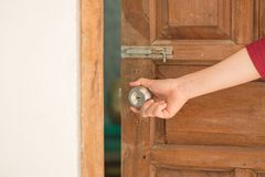 Manopola della porta aperta della mano delle donne o aprire la porta fotografia stock