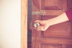 Manopola della porta aperta della mano delle donne o aprire la porta immagine stock
