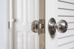 Manopola di porta inossidabile del primo piano, con la porta aperta leggermente Fotografia Stock Libera da Diritti