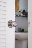 Manopola di porta inossidabile del primo piano, con la porta aperta leggermente Fotografie Stock