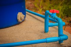 Manopola rossa della valvola a sfera del PVC sulla linea del tubo del PVC nello scandagliare sistema Immagine Stock