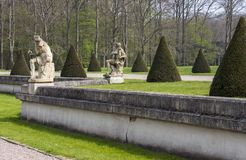 Manor garden with sculptures and trees. Manor garden with sculptures and coned trees stock photography