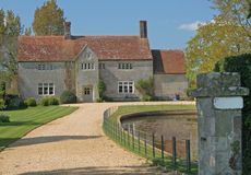 A manor house. An old English country manor house on a sunny day. With a long gravel drive and pond in the grounds Stock Photography