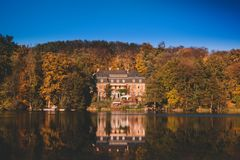 Manor house in autumn forest on the lake with reflection stock photography