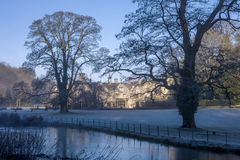 Manor House Hotel with two big trees along the river in Castle Combe in a winter morning Stock Photos