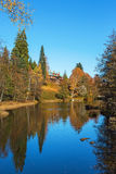 Manor house by the river in autumn landscape Stock Photo