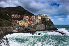 Manorolla in the Sun. Manorola in the Cinque Terre region of North Western Italy sits colorfully atop the cliffs while braving a late spring storm Royalty Free Stock Photo