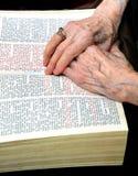 Manos abrochadas en la biblia imagen de archivo