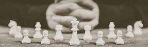 Manos abrochadas que planean estrategia con las figuras del ajedrez fotografía de archivo