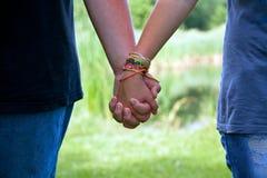 Manos adolescentes de la explotación agrícola de los pares de la edad, amor del verano Fotos de archivo libres de regalías