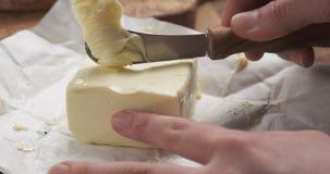 Manos adolescentes femeninas que raspan la mantequilla con un cuchillo Fotografía de archivo libre de regalías
