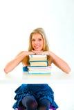 Manos adolescentes sonrientes de la explotación agrícola de la muchacha en pilas de libros Fotos de archivo libres de regalías