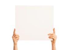 Manos aisladas que llevan a cabo un trozo de papel grande Foto de archivo