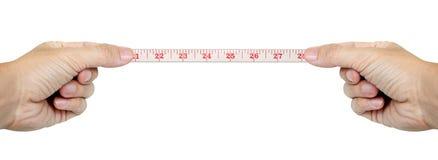 Manos aisladas que miden por cinta métrica Imagen de archivo