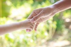 Manos amigas - hombre que lleva a cabo la mano del niño Foto de archivo libre de regalías
