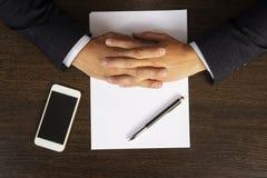 Manos apiladas en la mesa durante negociaciones Una hoja de papel en el escritorio y el teléfono Reunión de negocios Discusión imagen de archivo libre de regalías