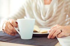 Manos arrugadas con una taza de café Imagen de archivo libre de regalías